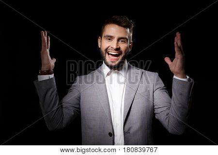 Rage angry young handsome man shouting closes ears with fingers over grey background. Copy space. Eyes closed.