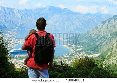 father with little daughter travel hiking in mountains at sea