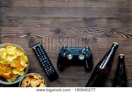 playing video games on console set with chips and beer on wooden desk background top view mock-up