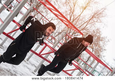 Two muscular men exercising on parallel bars, doing triceps dips. Winter fitness workout.