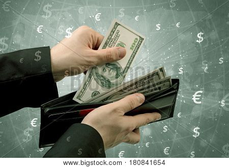 Businessman's hand takes out dollar from a wallet with global and exchange graphic