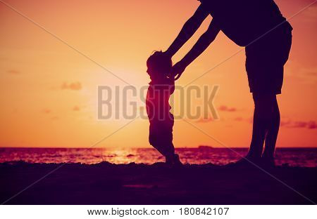 Silhouette of father and little daughter learning to walk at sunset