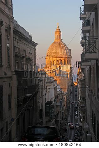 church dome of valletta, malta, in golden evening sunlight
