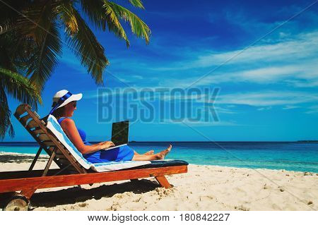 young woman with laptop on beach, remote work concept