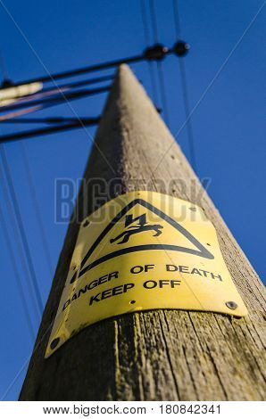 warning yellow electrocution sign on electrical pole against blue sky
