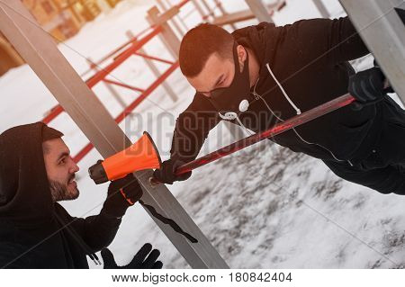 Two male adults training outdoors. Fitness coach yelling through loudspeaker while sporty man wearing high altitude mask exercising on bars.