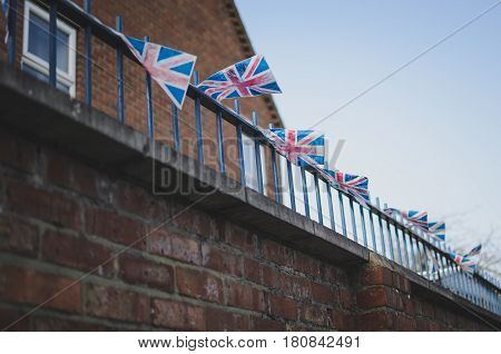 small union jack flags on a balcony in windy cold weather. typical british red brick building in the background