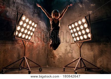 Portrait of beautiful attractive blonde young woman dancer on the stage with lights in loft background dancing free dance