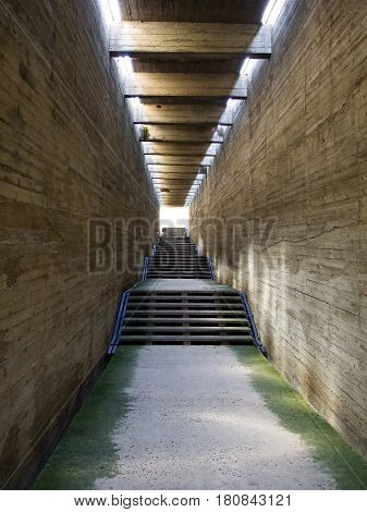 Stone walls and stone ladder, the road it is concreted, a ceiling from a stone, the room, construction, brown color, are expensive a green moss on each side, the ladder conducts up,  light  at the end