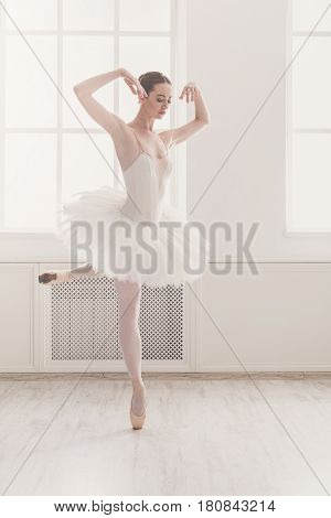 Classical Ballet, ballerina on pointe. Beautiful graceful dancer practice ballet positions in tutu skirt near large window in white light hall. Training, high-key soft toning.