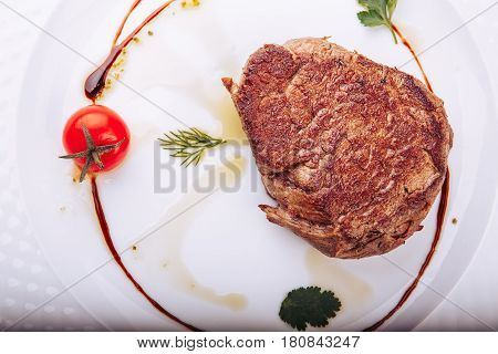 Grilled T-Bone Steak on white plate on dark wooden background.