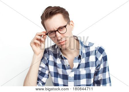Distrustful man looking at camera touching the glasses isolated on white