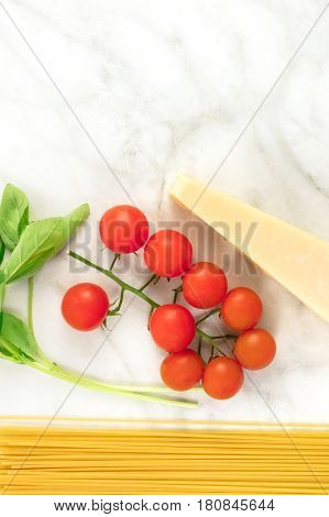 An overhead photo of basic pasta ingredients on a white marble table. Fresh cherry tomatoes, a slice of cheese, spaghetti, and basil leaves, with a place for text