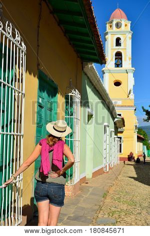 Tourist on the city tour in Trinidad is looking at the tower of the San Francisco de Asis Church being by the main square in the most tourist city Trinidad on Cuba