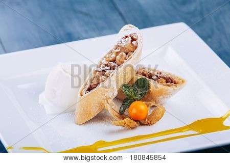 Homemade apple strudel with fresh apples, nuts and powdered sugar on a blue vintage wooden background. Apple strudel with vanilla ice cream.