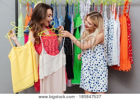 Two young beautiful women choosing the best dress near hanger with clothes