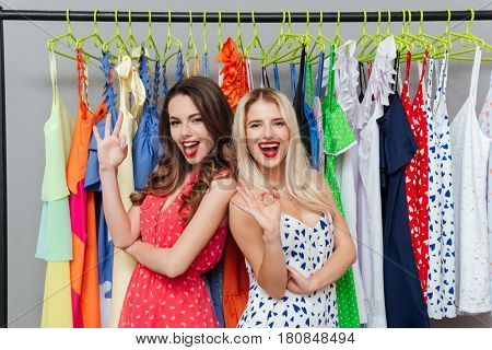 Cheerful young woman standing near rack with clothes showing okay gesture