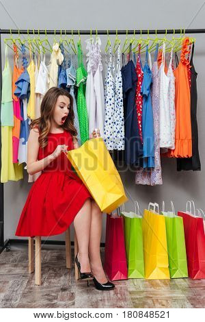 Surprised young woman in red dress looking into package sitting near hanger with dresses