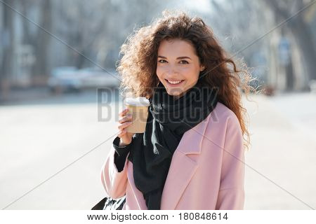 Cheerful young woman wearing pink coat walking in the sunny city street and drinking take away coffee in paper cup.