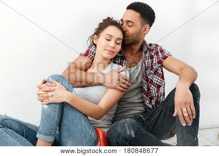 Picture of young cheerful loving couple sitting on floor in new flat makes repair.