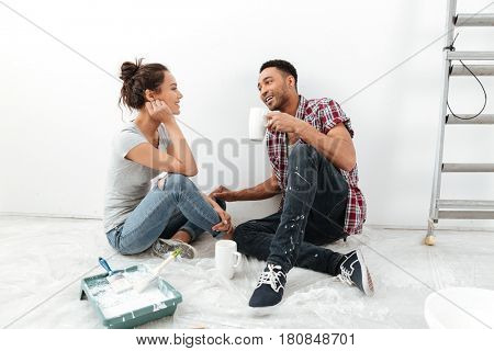 Picture of smiling young loving couple sitting on floor in new flat makes repair. Looking aside while drinking tea.