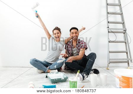 Photo of young happy loving couple sitting on floor in new flat makes repair. Looking at camera.