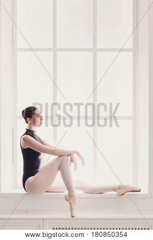 Beautiful ballerina portrait on window sill. Graceful ballet dancer in high-key, copy space