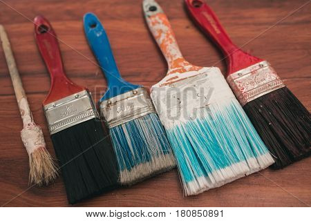 Multicolored brushes in paint lie on a wooden background. Up view