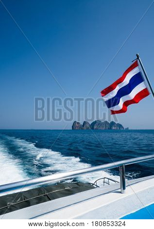 Thai flag on the boat over beautiful sea and summer blue sky background. Thailand flag on ferry heading to Phi Phi islands