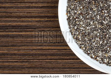 Chia seeds on white porcelain plate wood background table.