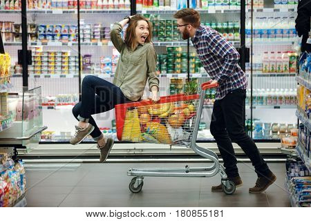 Happy cheerful couple having fun while choosing food in the supermarket. Young happy man pushing shopping cart with his girfriend inside