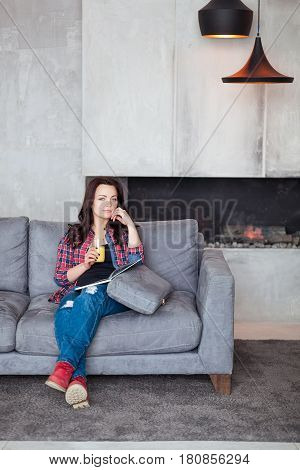 Young Woman Relaxing at Home with a Glass of Orange Juice. Beautiful girl in a casual style sits on the sofa and reads a book at loft style home.