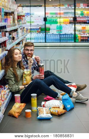 Portrait of a hungry happy couple sitting on the supermarket floor and eating snacks