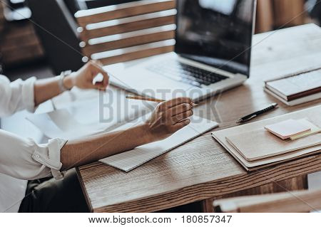 Busy working day. Close-up of African woman working with her note pad and laptop while sitting in restaurant