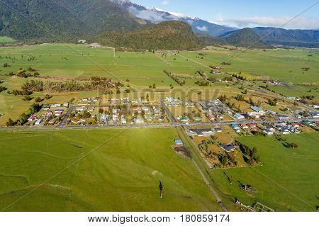 Aerial view of small New Zealand village town surrounded by green fields and farms. Whataroa South Island. New Zealand
