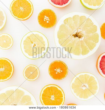 Pattern of fresh fruits - lemon, orange, mandarin, grapefruit and sweetie on white background. Flat lay, top view.