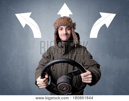 Young man holding black steering wheel with three arrows above his head pointing in different directions