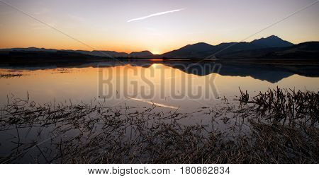 Beautiful colorful sunset at lake Liptovska Mara and mountains at backround