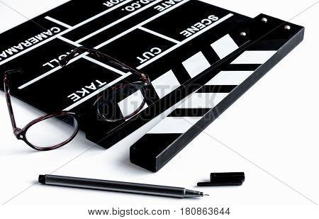 Screenwriter desktop with movie clapper board on white background