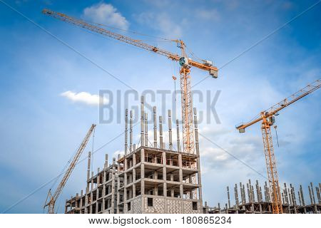Modern houses under construction and industrial construction cranes
