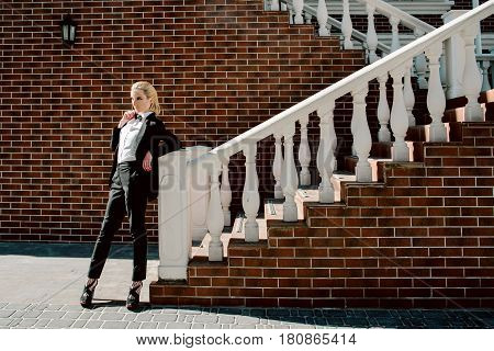 Portrait of stylish fashionable beautiful blonde woman in man black suit with bow tie outdoor nearly wall, staircase, lantern
