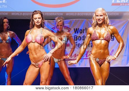 MAASTRICHT THE NETHERLANDS - OCTOBER 25 2015: Female fitness bikini models show their best front pose at championship on stageat the World Grandprix Bodybuilding and Fitness of the WBBF-WFF