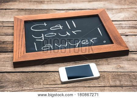 Smartphone And Chalkboard In Wooden Frame With Text - Call Your Lawyer On Wooden Tabletop, Law Conce