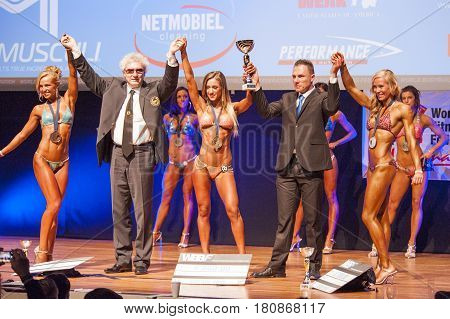 MAASTRICHT THE NETHERLANDS - OCTOBER 25 2015: Female bikini figure models celebrate their victory with officials at the World Grandprix Bodybuilding and Fitness of the WBBF-WFF