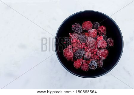 Frozen Berries in black bowl on white marble surface