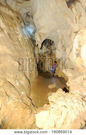 Vang Vieng Laos - 15 January 2012: boy with a flashlight in Tham Jang (Chang Cave) at Vang Vieng on Laos