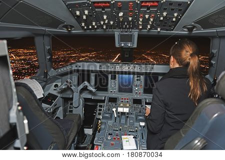 Cockpit of modern plane during flight over glowing night city. Pilot navigating it