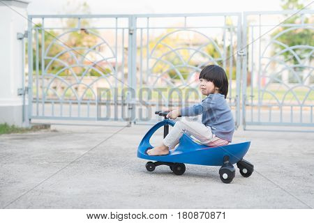 Cute Asian child driving blue toy car outdoors