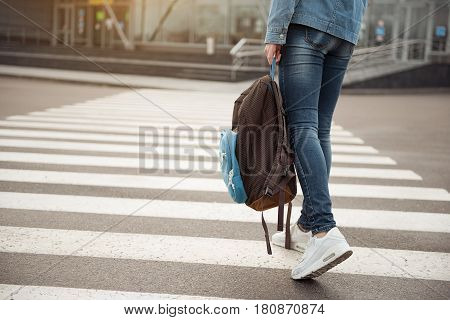 Close up of legs of woman. She holding bag in arm while crossing over road. She is traveler