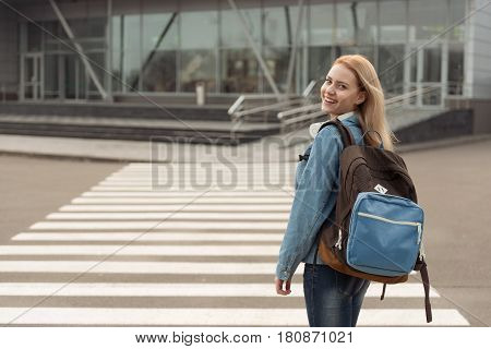 Portrait of female tourist demonstrating gladness while stepping across route in outdoors. She keeping big backpack